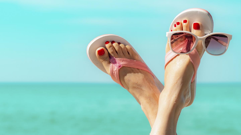 Schöne Füße: Gepflegte Frauenfüße mit rotem Nagellack in rosa-weißen Flipflops für türkisfarbenem Meer und hellblauem Himmel.